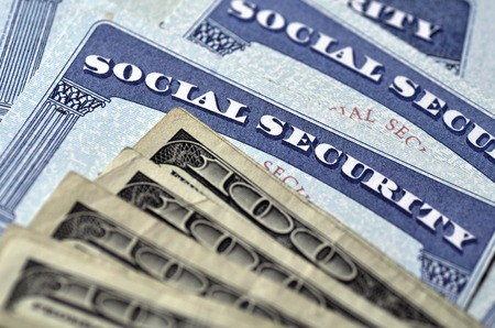 31405883 - detail of several social security cards and cash money symbolizing retirement pensions financial safety